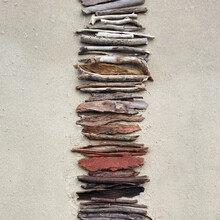 Overhead View Of Driftwood In A Row On Sand Background