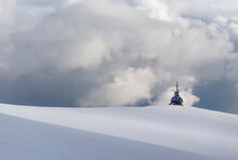 Windmill On Snow Covered Mountain Against Sky In Rodnei Mountains