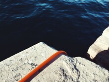Close-up High Angle View Of An Orange Hose Disappearing Over A Wall Into The Sea