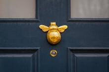 A Golden Bumblebee As A Door Knocker On A Dark Wooden Front Door