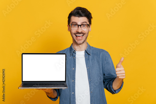 Amazed excited cheerful caucasian unshaven guy in glasses and denim shirt holds open laptop with blank white screen, showing thumbs up gesture, standing on isolated orange background, friendly smiling