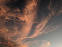 Low Angle View Of Dramatic Desert Sky With Swirly Orange Clouds At Sunset
