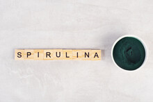 Spirulina Powder On A Gray Table, Top View, Inscription Spirulina