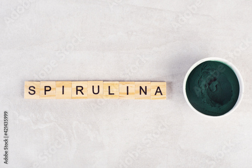 Fototapeta spirulina powder on a gray table, top view, inscription spirulina obraz