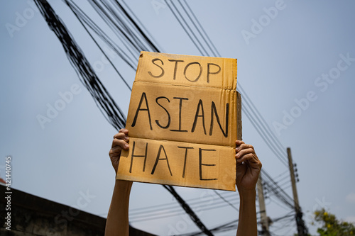 Obraz A man holding Stop Asian Hate sign - fototapety do salonu