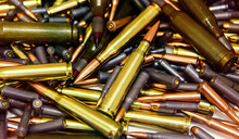 Pile Of Bullets With Copper Tips Under A Warm Light. Close Up Of A Lot Of Bullets. Gun Violence In America. Ammunition Rifle Or Pistol.