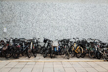 Bicycles Parked On Street Against Wall