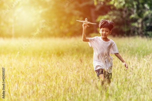 Fotografia Cute Asian child playing airplane in the park outdoors Happy Asian boy holding a plane runs in a meadow with sunset