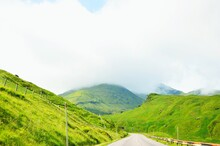 Road Amidst Green Landscape Against Sky
