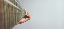 Close-up Of Hand Holding Guitar Against Wall