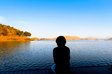 Rear View Of Silhouette Woman Looking At Lake Against Sky