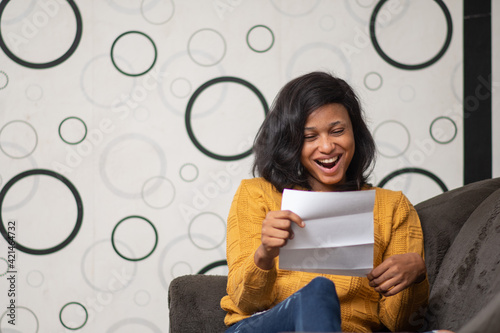 Obraz young black woman looks very happy reading a letter - fototapety do salonu