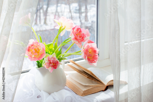 Fototapeta still life a vase with tulips and an old book on the window obraz