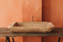 Minimalistic Interior Style. Vintage Sink On A Wooden Shelf At The Orange Grunge Wall Background.