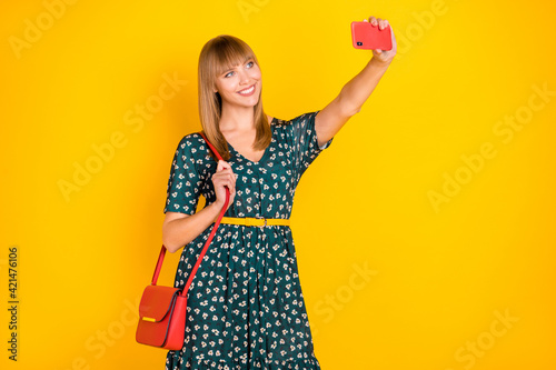 Portrait of attractive cheerful girl taking making selfie posing trip journey isolated over bright yellow color background