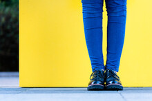 Low Section Of Woman Standing Against Yellow Wall