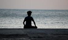 Silhouette Man Sitting On Beach Against Clear Sky