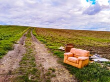 Scenic View Of Agricultural Field Against Sky With An Armchair In The Foreground