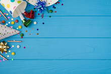 Top View Photo Of Birthday Party Composition In Upper Left Corner Ribbon Stars Candles Hat Confetti Pipes In Polka Dots Paper Cup And Plate On Isolated Blue Wooden Table Background With Copyspace
