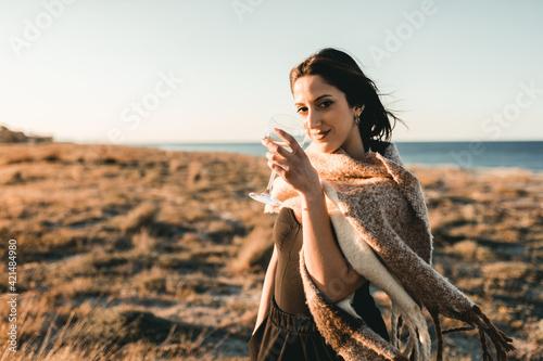 Leinwand Poster Bella ragazza tiene in mano un calice di vino bianco sulla spiaggia