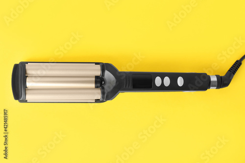 Modern triple curling iron on yellow background, top view Wallpaper Mural