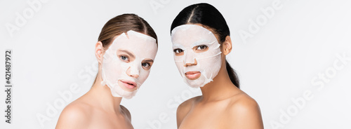 Obraz young interracial women in moisturizing sheet masks isolated on white, banner - fototapety do salonu