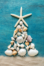 Christmas Tree Made From Sea Shells And Starfish On Wooden Blue Background, Top View