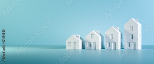 Canvas Print Which size of house can you afford? Concept shot: four differently sized models of houses on a blue background