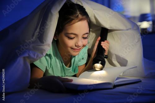 Little girl with flashlight reading fairy tale in dark bedroom