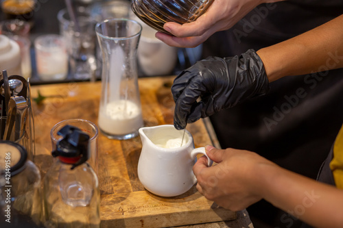 Fototapeta A white ceramic cup containing milk and bartender ingredients is mixing milk-related drinks. obraz