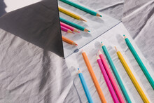 High Angle View Of Colored Pencils On Table By Mirror