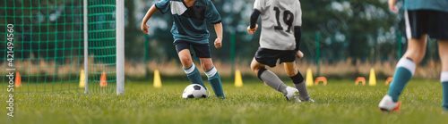 Fototapeta Soccer players on training pitch. Group of young footballers in a duel. Soccer kids running ball in a practice match. School kids playing game on summer training camp obraz
