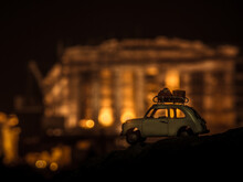 Toy Vehicle Car Against Illuminated Built Structure, Parthenon Of Acropolis In Athens, At Night