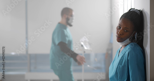 Photographie Exhausted african nurse leaning on hospital corridor wall and removing safety ma