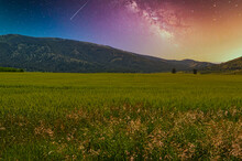 Shot Of A Beautiful Colorful Sky Full Of Stars Of The Milky Way Galaxy In The Field Full Of Grass.