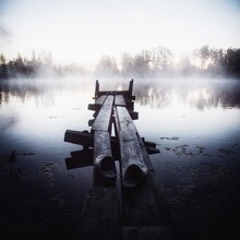 Broken Pier On Lake Against Sky During Foggy Weather