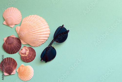 Summer composition with sunglasses and Japanese sea scallop seashells on a blue background Fototapet