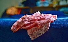 A Pair Of Pretty Pink Panties, On The Corner Of A Bed.