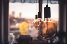Selective Focus Shot Of Light Bulbs Hanging In A Row Over A Kitchen Table