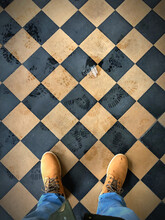 Low Section Body Of A Man With Blue Jeans And Winter Boots On A Tiled Checkerboard Pattern Floor