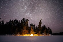 Trees And Tent On Snow Covered Land Against Starry Sky At Night