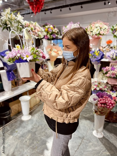 girl wearing a protective mask at a flower shop. Covid-19 Fototapete