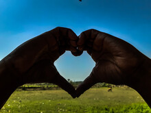 Cropped Image Of Hand Holding Heart Shape Against Blue Sky