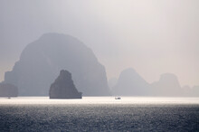 Scenic View Of Sunrise Over Ha Long Bay In Vietnam With Fishing Boat In The Distance