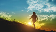 Silhouette Woman Walking On Hill Against Sky During Sunset