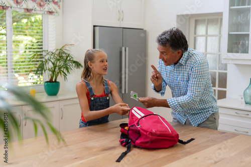 Caucasian grandfather giving granddaughter packed lunch and lollipop in kitchen