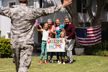 Caucasian Soldier Father And Family Meeting Outside Home With Welcome Sign And American Flags