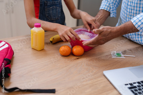 Midsection of caucasian grandfather giving granddaughter packed lunch and lollipop in kitchen