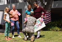 Caucasian Soldier Father Greeting Family With Welcome Sign And American Flags Outside Home