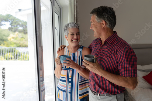 Smiling senior caucasian couple standing by window embracing holding cups of coffee